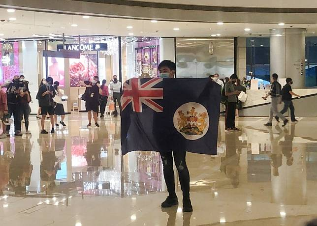有人展示殖民地時代香港旗。(黃雄攝)