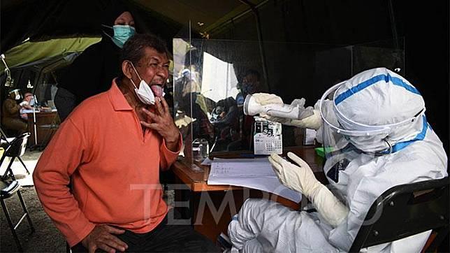 Dokter memeriksa rongga mulut pasien bergejala dan memiliki riwayat kontak erat dengan warga positif Covid-19 sebelum tes swab PCR di sebuah Puskesmas di Bandung, Senin, 14 Juni 2021. Tes PCR terus digencarkan di tengah ancaman ledakan kasus penularan Covid-19 di Bandung Raya yang mencapai 261 persen. TEMPO/Prima Mulia