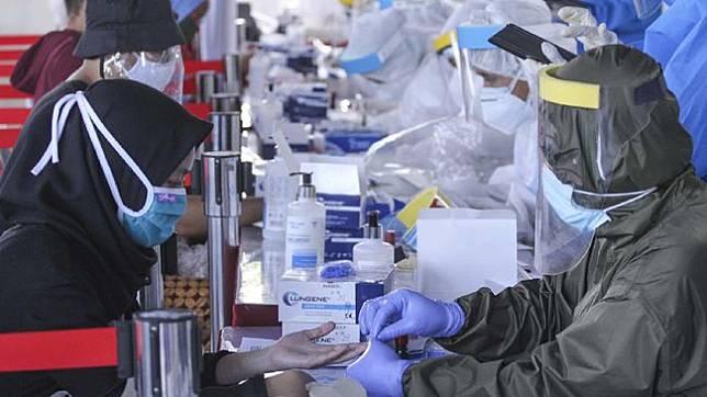 Petugas Medis mengambil sampel darah warga saat rapid test massal di Depok, Jawa Barat, Jumat (22/5). (ANTARA FOTO/ASPRILLA DWI ADHA)