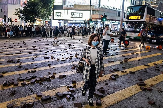 Pedestrians walk over scattered bricks during a protest in Causeway Bay, Hong Kong on Nov. 12. Photographer: Justin Chin/Bloomberg