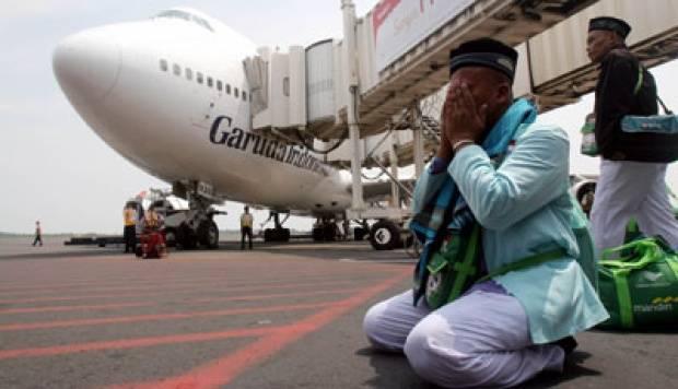 Sejumlah jamaah haji berdoa setelah turun dari pesawat Garuda Indonesia di Bandara Internasiona Juanda, Surabaya. TEMPO/Fully Syafi