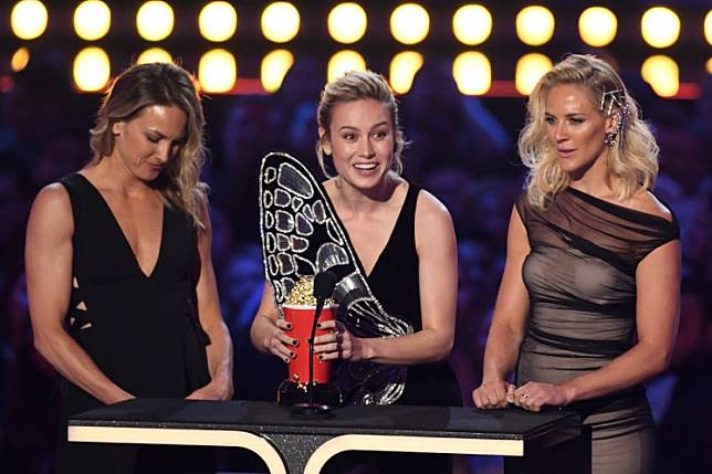 US actress Brie Larson (C), flanked by her stunt doubles Joanna Bennett and Renae Moneymaker, accepts the award for Best Fight for 'Captain Marvel' during the 2019 MTV Movie & TV Awards at the Barker Hangar in Santa Monica on June 15, 2019.