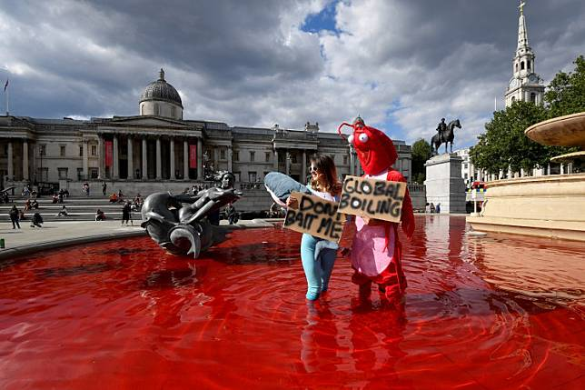 Animal rights and environmental activists hold signs as they stand inside a fountain whose water was turned red after protesters poured colored dye into the clear water, on Trafalgar Square in London, Britain, on July 11, 2020.