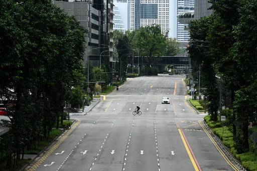 A cyclist rides across a quiet street in the central business district of Singapore on April Tuesday, as the country ordered the closure of all businesses deemed non-essential as well as schools to combat the spread of the COVID-19.