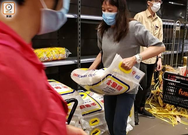 職員補充貨架後,市民搶購食米。(朱先儒攝)