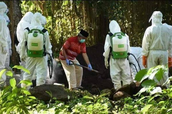 Wali Kota Tidore Kepulauan, Ali Ibrahim menaburkan tanah di atas makam istrinya Salama yang meninggal akibat covid-19, Senin (1/6/2020).