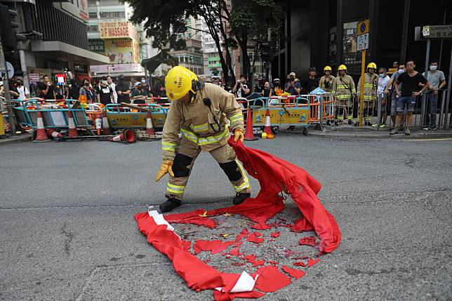 A fireman collects the remains of a burned Chinese flag during a protest on Sept. 15. Photographer: Kyle Lam/Bloomberg