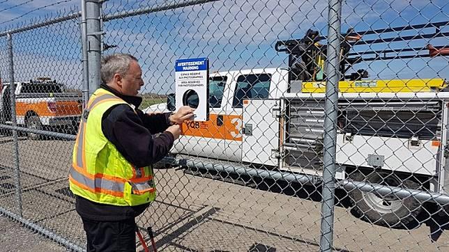 為方便大家影飛機,YQB Aviation 機場決定在鐵絲網上加裝10塊中間設有圓洞的鐵板。(互聯網)