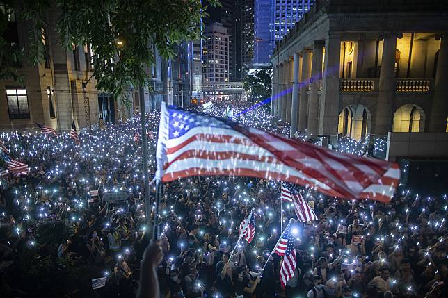 Demonstrators wave U.S. flags during a rally in support of the Hong Kong Human Rights and Democracy Act, Oct. 14. Photographer: Chan Long Hei/Bloomberg