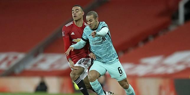 Mason Greenwood berduel berebut bola dengan Thiago Alcantara di laga antara Manchester United vs Liverpool di Old Trafford, Senin (25/01/2021) dini hari WIB. (c) Pool PA via AP Photo