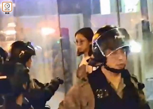 一名女子在始創中心外指罵防暴警,被警員包圍截查。(葉嘉文攝)