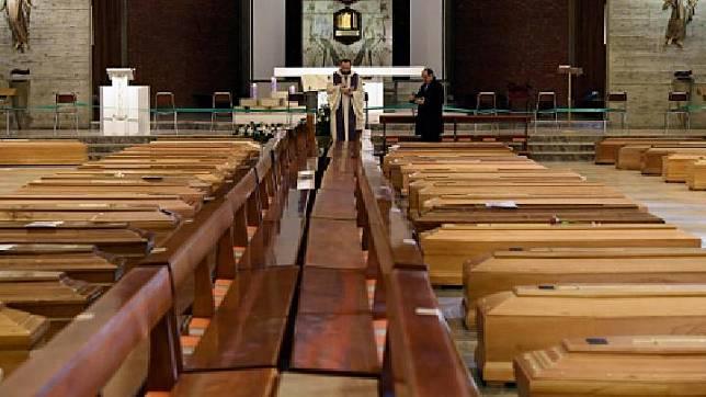 Pendeta memberkati peti jenazah korban virus corona atau Covid-19 yang akan diangkut menggunakan truk militer di Seriate, Italia, 28 Maret 2020. REUTERS/Flavio Lo Scalzo