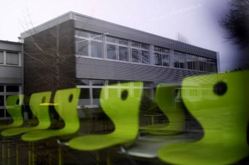 A school building is reflected in the window of a classroom with chairs standing on tables at a closed school in Gangelt near Heinsberg, western Germany, on February 27, 2020. Children daycare facilities, schools and administrative offices have been closed in the area around Heinsberg after a couple of the area contracted the coronavirus disease.