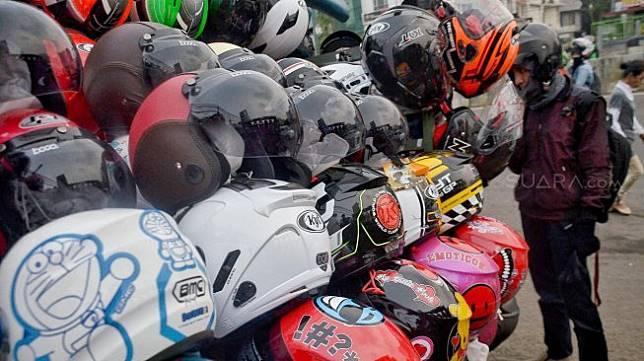 Pengunjung melihat jajaran helm yang dijual oleh pedagang. [Suara.com/Muhaimin A Untung]
