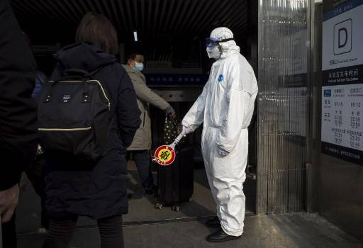 Security personnel wearing protective clothing to help stop the spread of a deadly virus which began in Wuhan, stands at a subway station in Beijing on Sunday, Jan. 26, 2020. China on Jan. 26 expanded drastic travel restrictions to contain a viral epidemic that has killed 56 people and infected nearly 2,000, as the United States, France and Japan prepared to evacuate their citizens from a quarantined city at the outbreak's epicenter.