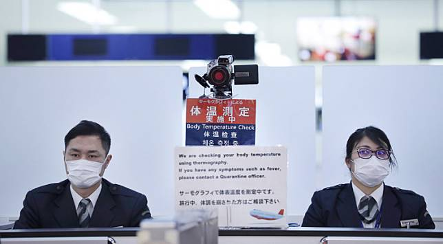 In this picture taken on January 16, 2020, officers work at a health screening station as they observe passengers arriving on a flight from Wuhan, China, where a SARS-like virus was discovered and has since spread, at Narita airport. - The death toll from a new China virus that is transmissible between humans rose to six, the mayor of Wuhan said in an interview with state broadcaster CCTV on January 21, as the World Health Organization said it would consider declaring an international public health emergency over the outbreak. (Photo by STR / JIJI PRESS / AFP) / Japan OUT
