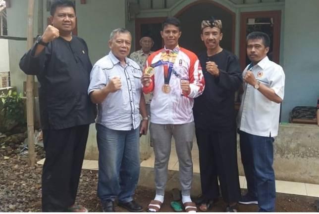 Muahammad Taufik (32) atlet asal Kabupaten Tasikmalaya yang meraih medali emas di Sea Games Filiphina bersama Koni dan pejabat daerah setempat di rumahnya, Selasa (10/12/2019).(KOMPAS.COM/IRWAN NUGRAHA)  Artikel ini telah tayang di Kompas.com dengan judul