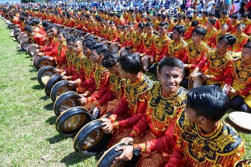Performers take part in the Rapa'i Geleng dance, using a traditional tambourine, to celebrate Indonesia's 74th Independence Day in Blang Pidie, Aceh province on August 17, 2019.