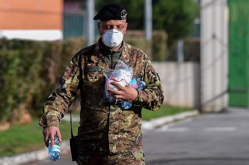 A military personnel handling respiratory masks walks across the Cecchignola quarantine center, south of Rome, on Feb. 3, where Italian citizens have been placed in quarantine after being repatriated from the coronavirus hot-zone of Wuhan at the nearby military airport of Pratica di Mare.