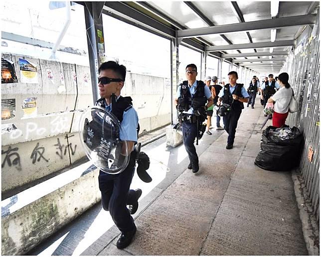 帶備盾牌和頭盔的警員九龍灣「連儂牆」呼籲不要在場逗留。