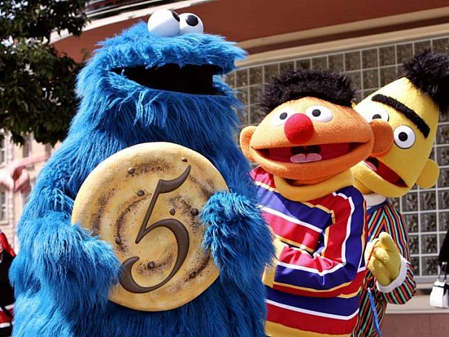 In this file photo taken on April 20, 2006 Sesame Street character Cookie Monster shows a large cookie with the figure five to celebrate the fifth anniversary of Hollywood theme park Universal Studios Japan in Osaka, while other characters Earnie (C) and Bert (R) smile.