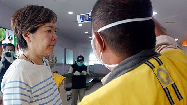 Petugas Karantina Kesehatan memeriksa suhu tubuh wisatawan asal Cina (kiri) yang baru mendarat di bandara DEO Kota Sorong, Papua Barat, Ahad, 26 Januari 2020. Pasien suspect virus corona tersebut akan diisolasi selama kurang lebih tujuh sampai 14 hari. ANTARA/Olha Mulalinda