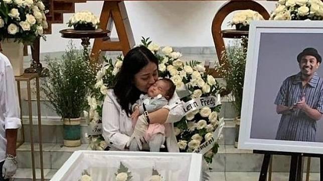 Istri Glenn Fredly, Mutia Ayu menggendong sang putri di tepi peti jenazah suami. [Twitter @haibebyjo]