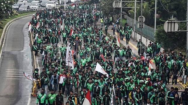 Sejumlah pengemudi ojek online yang tergabung dalam Gabungan Aksi Roda Dua Indonesia (Garda) berjalan menuju gedung DPR untuk melakukan aksi unjuk rasa, Senayan, Jakarta Pusat, 23 April 2018. TEMPO/Fakhri Hermansyah
