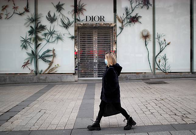 A woman wearing a protective face mask walks past the closed Dior shop on the Champs Elysees in Paris