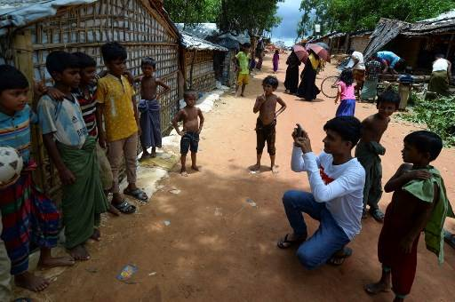 In this picture taken on July 23, 2019, Rohingya youth Mohammad Rafiq (2nd R, in white) uses his mobile phone to take photos of children at the Kutupalong refugee camp. Rafiq, 19, one of 30 Rohingya youths selected by the World Food Programme for its