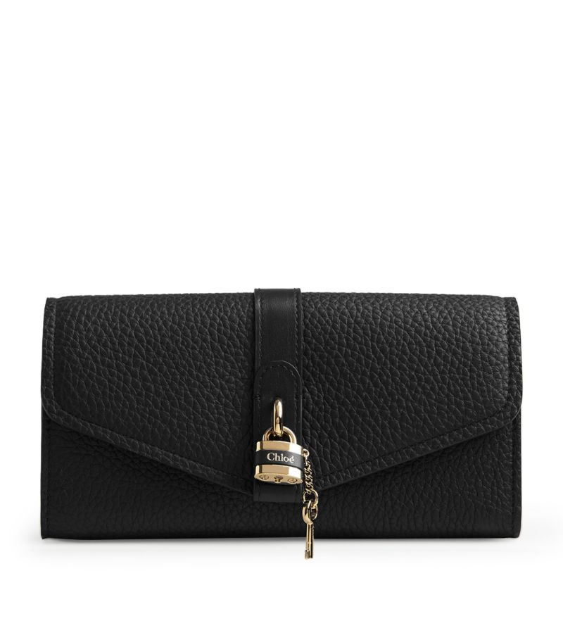Chloés Aby bags are defined by their logo-punctuated lock-and-key detail - Natacha Ramsay-Levis reincarnation of the iconic padlock from the Paddington bag - and this wallet iteration keeps the adornment front and centre. Realised in grained calfskin with a longline envelope silhouette that opens to an expertly organised interior, its an accessory for the woman with much to carry.