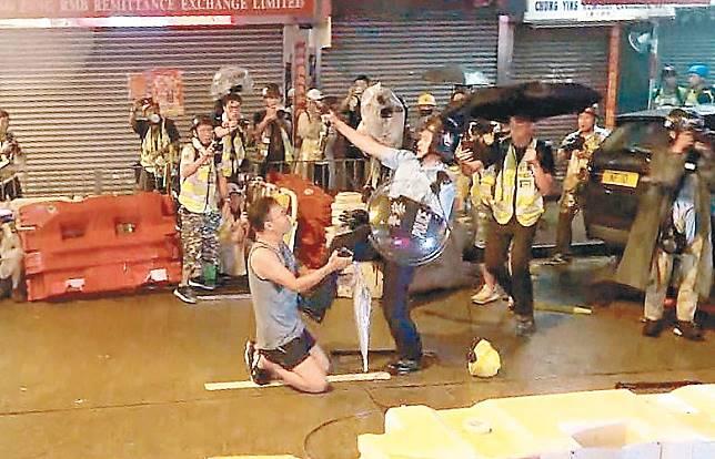 持槍警員為免示威者再衝前施襲,踢開跪地街坊。