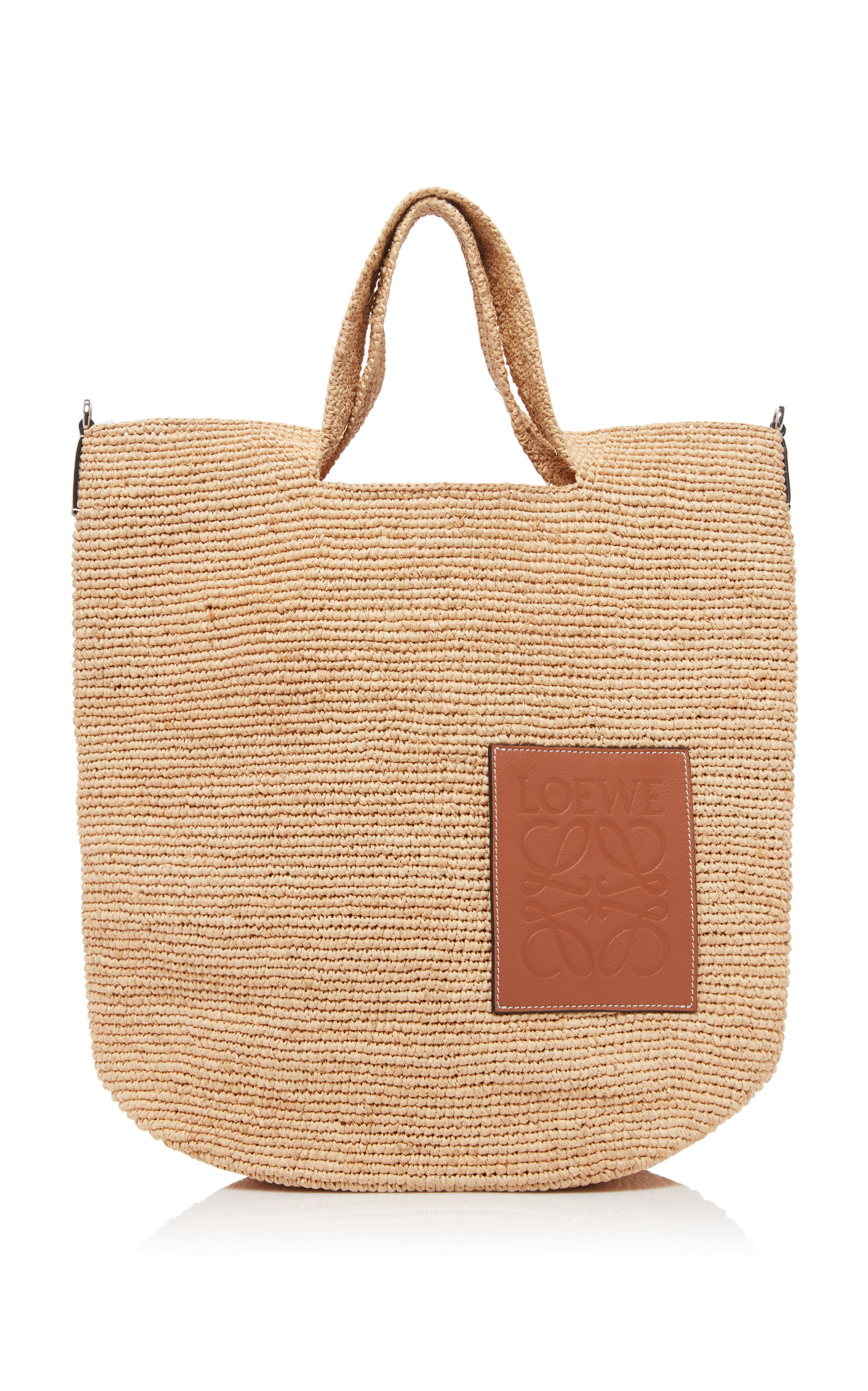 Expertly designed with impeccable craftsmanship, Loewe's 'Slit' tote is made in an oversized design for carrying your larger belongings. It's woven from natural raffia straw for a relaxed shape and embellished with a leather panel that's stamped with the label's iconic logo-anagram. Attach the optional shoulder strap for wear across the body.
