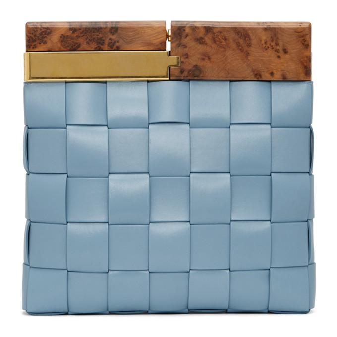 蓝色手拿包,采用小羊皮面料 Intrecciato 编织设计,铰链开合处棕色木质饰边。金色和银色五金。尺寸约为:长 28cm x 高 26.5cm x 宽 5cm。供应商配色:Ice