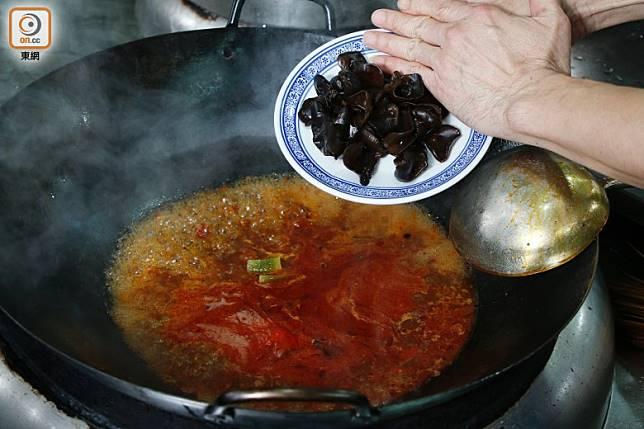 辣醬油入味後將黑木耳、魷魚等材料慢慢放入熬煮。(郭凱敏攝)