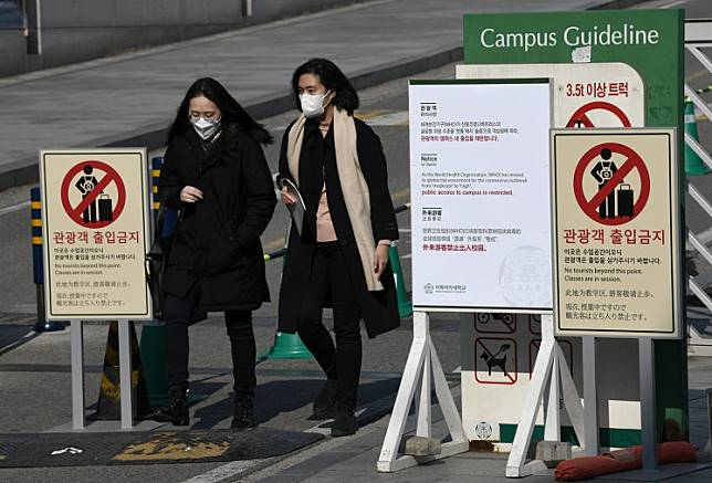 People wearing face masks walk past a 'no tourists' sign amid concern over the spread of the SARS-like virus, at the main entrance of a university in Seoul, South Korea on Feb. 4, 2020.