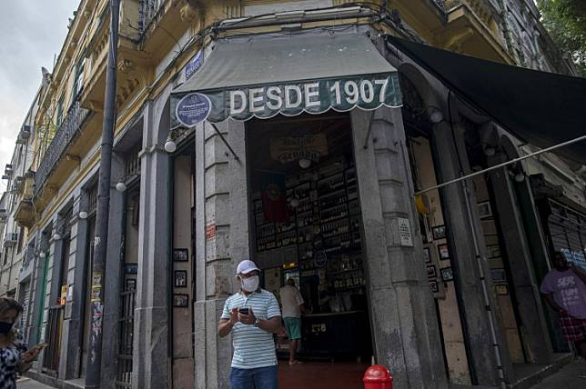 A man wearing a face mask leaves the centenary bar Armazem Senado in Rio de Janeiro, Brazil, on July 2, 2020 as the city's bars and restaurants reopened after more than three months of lockdown to fight the COVID-19 novel coronavirus pandemic.