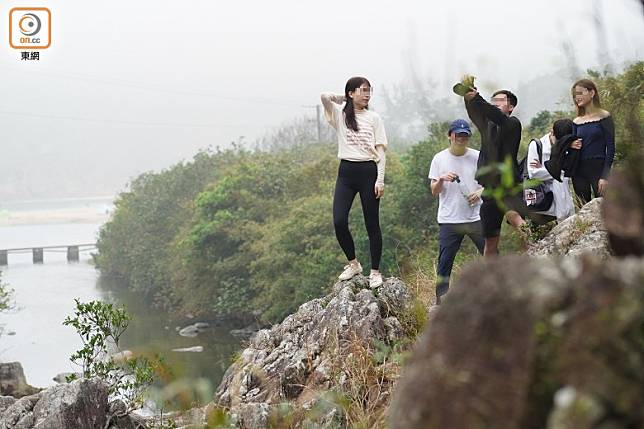 有行山市民不懼危險攀岩,站立於懸崖邊緣「打卡」留念。
