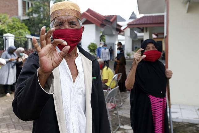 A senior citizen at the Rumoh Seujahtra Geunaseh Sayang nursing home in Banda Aceh, Aceh, poses while wearing a mask to prevent COVID-19 transmission on May 1.