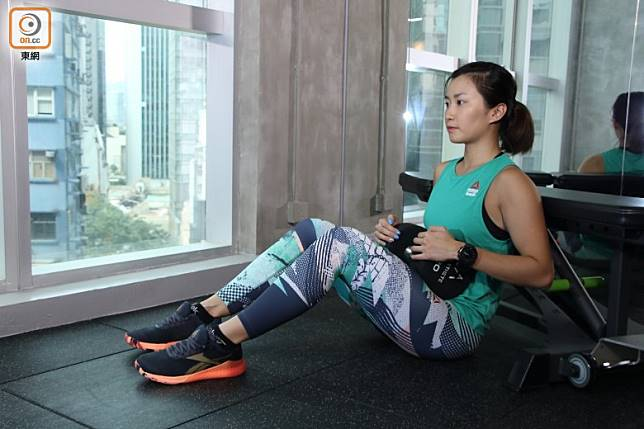 雙腳曲起坐於地上,背部緊貼健身椅,將啞鈴放於腹部位置。(張錦昌攝)