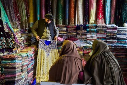 In this picture taken on Feb. 12, 2020, Afghan refugee women shop for clothing in a store in a bazaar at a neighborhood locally known as 'mini Kabul' in Peshawar. Pakistan is one of the largest refugee-hosting nations in the world, home to an estimated 2.4 million registered and undocumented people who have fled Afghanistan, some as far back as the Soviet invasion of 1979.