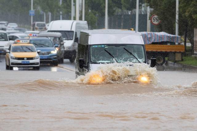 A vehicle travels through a flooded section of a road following heavy rainfall in Wuhan, Hubei province, China July 6, 2020.