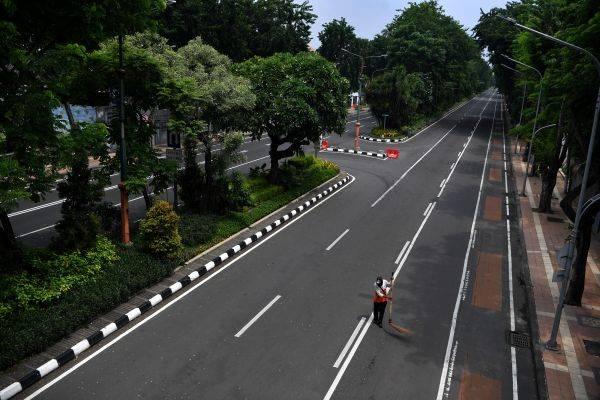 Seorang petugas kebersihan menyapu jalan di Jalan Darmo yang ditutup, Surabaya, Jawa Timur, Sabtu (28/3/2020).