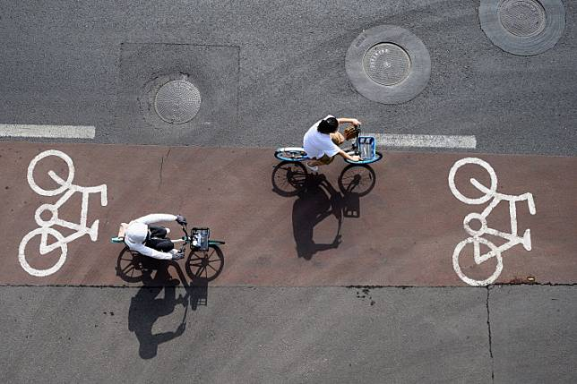 People pedal on a bicycle lane along a street in Beijing on July 5, 2020.