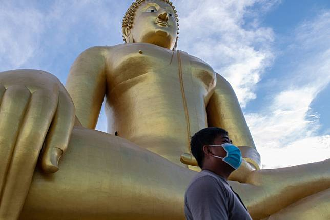 In this photo taken on July 2, 2020, a visitor walks past the largest Buddha statue in Thailand, in Ang Thong province, north of Bangkok, as authorities reopened sites to tourists following lockdowns to halt the spread of the COVID-19 novel coronavirus.