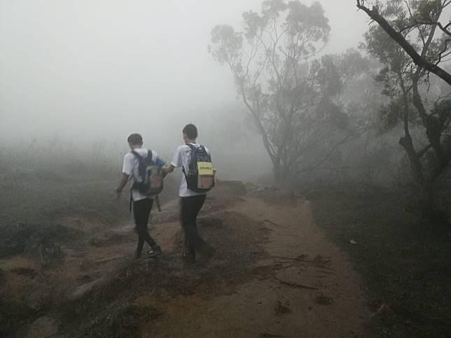 李同學帶領失明的盛軒走過山路。