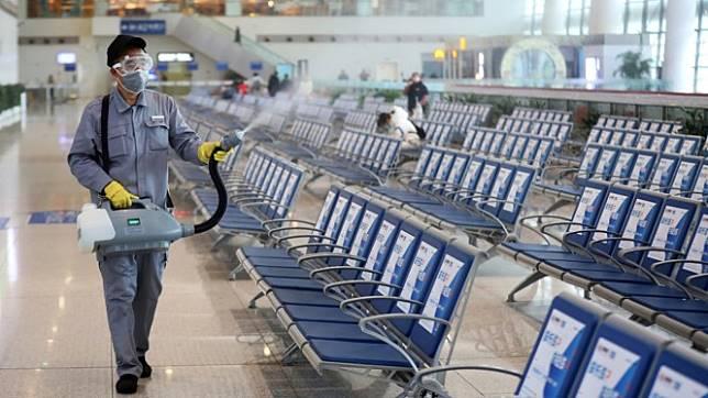 Petugas membersihkan area bandara dari Virus Corona.