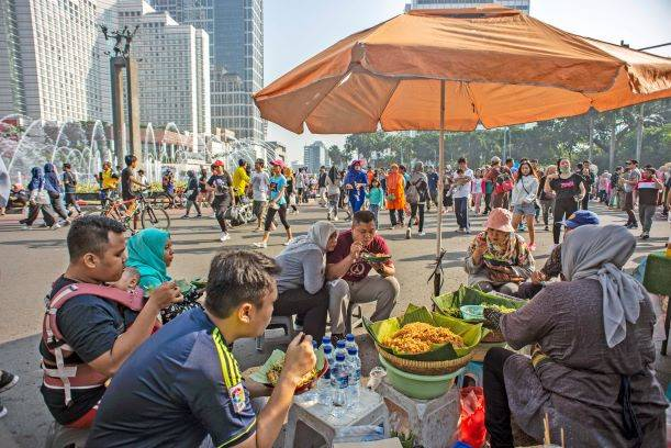Residents eat meals sold by street vendors during Car Free Day in the Hotel Indonesia traffic circle in Central Jakarta on May 5.