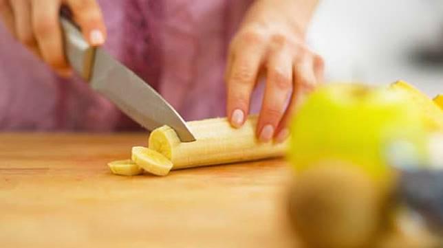 Ilustrasi seorang perempuan sedang mengiris pisang. [Shutterstock]