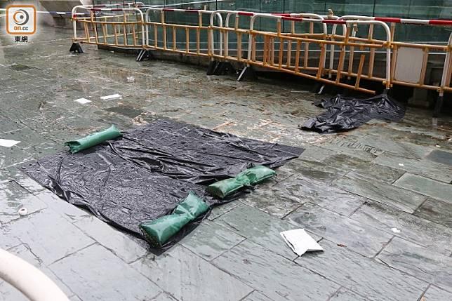 由於下大雨,警方用膠袋遮蓋血漬及狗臂架。(李健瑜攝)